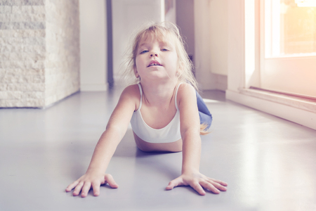 Little blond girl doing stretching exercises in the room near the window