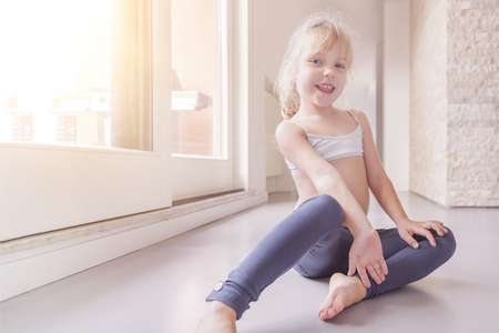 416c8bd98 Happy little blond girl in white top and blue leggings sitting on the floor in  the