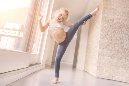 Little blond girl in white top and blue leggings doing gymnastic exercise in the room near the window