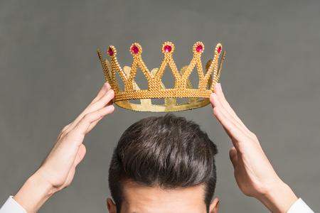 Homme brune tenant dessus de sa tête une couronne d & # 39 ; or sur un fond gris Banque d'images - 99067552