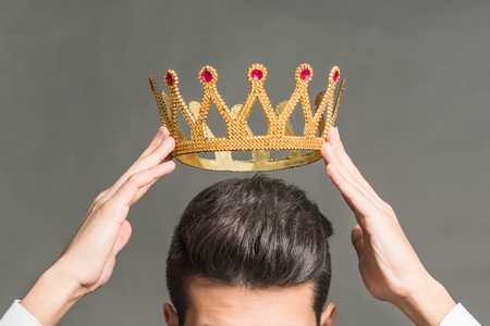 Man brunette holding above his head a golden crown on a gray background Stock Photo