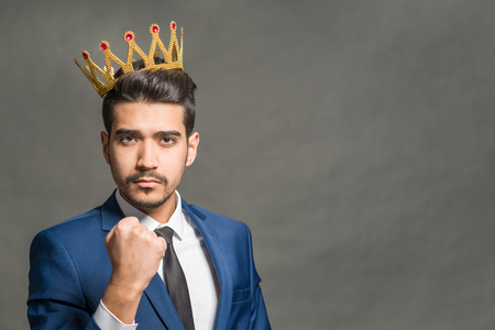Young attractive man in a blue suit with a crown on his head showing fist on a gray background Stock Photo