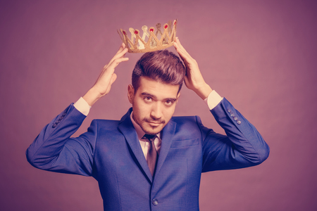 Young attractive man in a blue suit  holding above his head a golden crown on a purple background