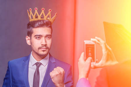 Young attractive man in a blue suit with a crown on his head photographed on phone in the sunlight