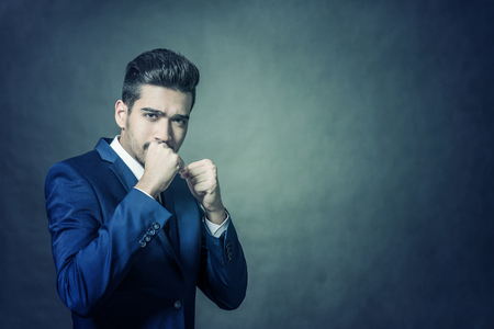 Young attractive man in a blue suit standing in a fighting stance. Toned Stock Photo
