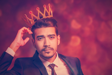 Young attractive man in a suit with a golden crown on his head on a red background with bokeh Stock Photo