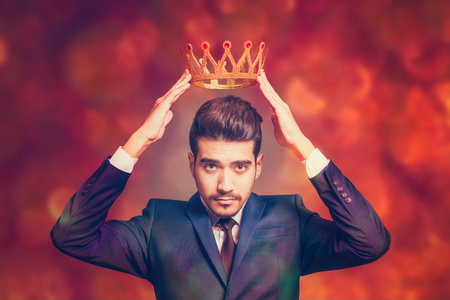 Young attractive man in a blue suit holding above his head a golden crown on a red background with bokeh Stock Photo