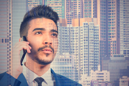 Young attractive man in a blue suit talking by the phone on the background of skyscrapers Stock Photo