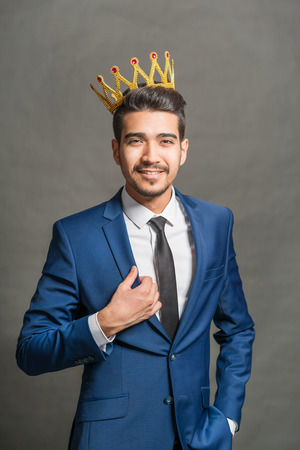 Young attractive man in a blue suit with a crown on his head on a gray background Stock Photo