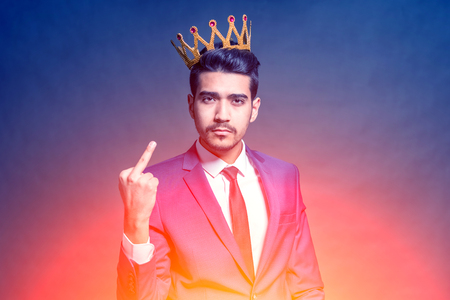 Young attractive man in a blue suit with a crown on his head showing middle finger in the bright glow