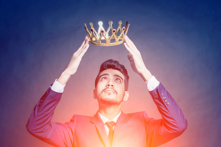 Young attractive man in a blue suit holding above his head a golden crown in the bright glow