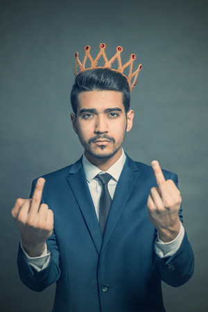 Young attractive man in a blue suit with a crown on his head showing middle fingers. Toned
