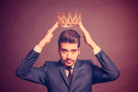 Young attractive man in a blue suit holding above his head a golden crown on a purple background Stock Photo