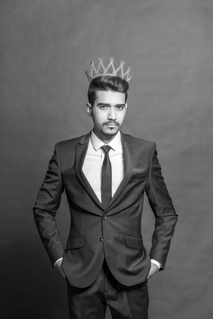 Young attractive man in a blue suit with a crown on his head. Toned