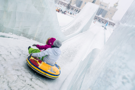 Two girls on a sled slide down the icy hill