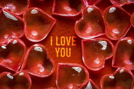Transparent glass hearts on a red leather background with an inscription I LOVE YOU