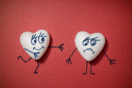 Two white hearts with happy and sad faces on red leather background
