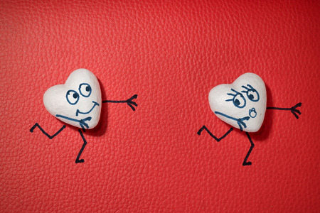Two white hearts with faces on red leather background