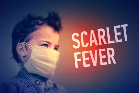 Boy in the medical mask covered his face with his hands next to inscription SCARLET FEVER Foto de archivo