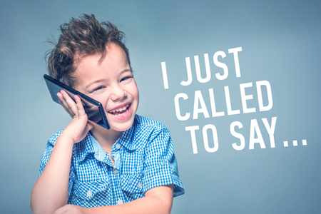 Cute little boy in a blue shirt talking on the phone next to inscription 'I JUST CALLED TO SAY'