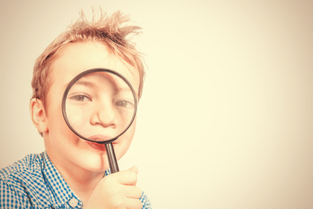 Boy holding a magnifying glass near the face on a beige background. Toned