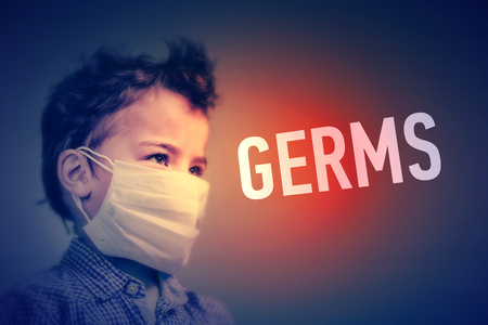 Boy in the medical mask covered his face with his hands next to inscription GERMS Stockfoto