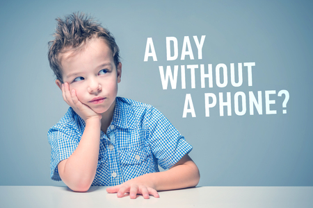 Cute thoughtful boy in a blue shirt at the table next to the inscription A DAY WITHOUT A PHONE Stockfoto