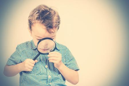 Cute boy in a blue shirt looking through a magnifying glass. Toned Reklamní fotografie