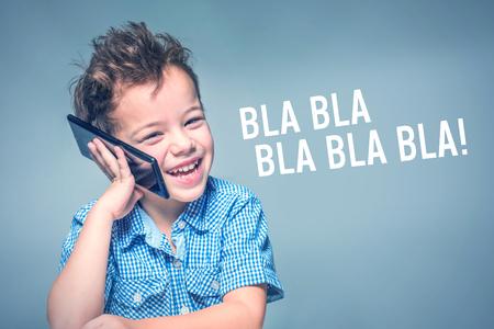 Cute little boy in a blue shirt talking on the phone next to inscription 'BLA BLA BLA'