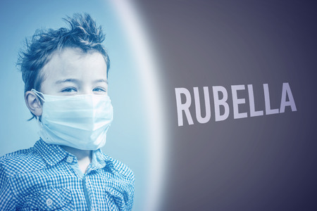 Boy in the medical mask next to inscription RUBELLA on brown background