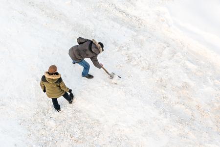 Two men cleans snow shovel, top view Stock Photo