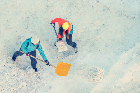 Two women in a bright jacket cleans snow shovel, top view. Toned