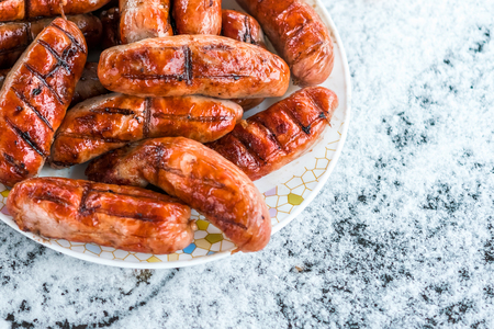 Sausages grill on the  plate in the snow 免版税图像