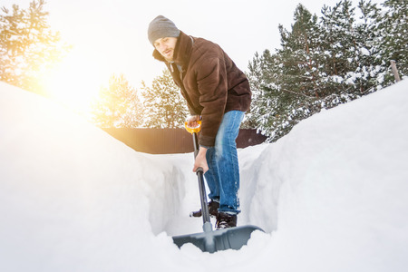 Man in winter clothes cleans snow shovel on courtyard at sunny day Stock Photo