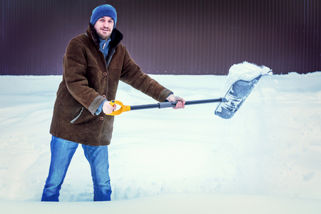 Man in winter clothes cleans snow shovel on courtyard. Toned Standard-Bild