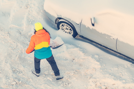 Woman in a bright jacket cleans snow shovel near the car