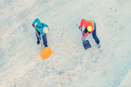 Two women in a bright jacket cleans snow shovel, top view Stock Photo