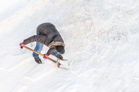 Man cleans snow shovel, top view