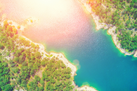 Top view of a lake surrounded by forest in the sunlight Stock Photo