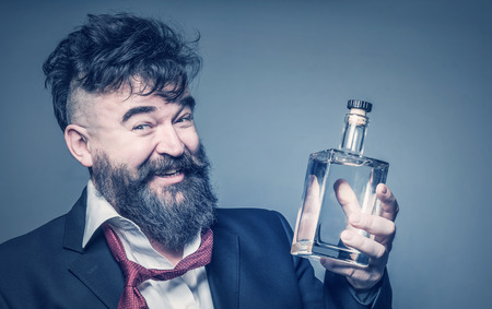 Cheerful drunk man with a beard holding a bottle of alcohol in his hand. Toned