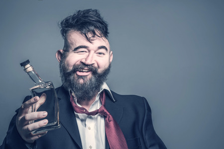 Distorted image of a bearded man in suit with a bottle of alcohol in his hand on a gray background