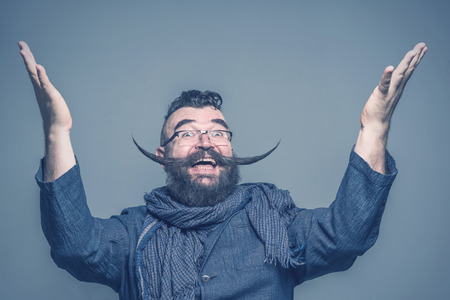 Crazy bearded man with a mohawk hairstyle and a very long mustache raising hands up. Toned