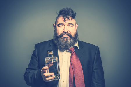 Disheveled adult bearded man in suit holding in his hand a bottle of alcohol. Toned