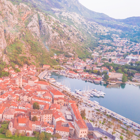 Old European city with a mooring for yachts at the foot of the mountains. Toned