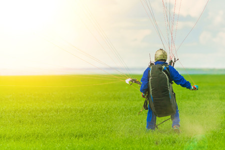 Man on a paraglider during a landing on a green field in the sunlight