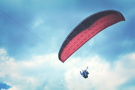 Red and black paraglider in the sky