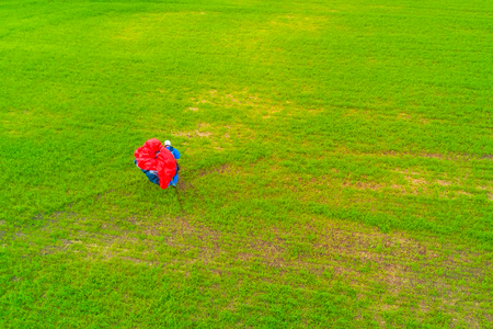 Top view of the man with a red paraglider on a green field