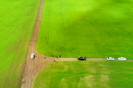 Top view of the green field and country road with cars and people