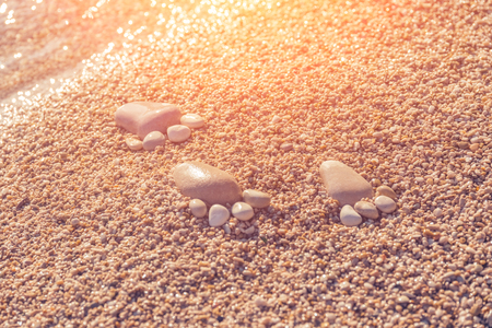 Footprint made of pebbles on the sand near the water in the sunlight