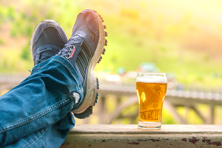 Legs in jeans and sneakers next to a mug of beer Stock Photo
